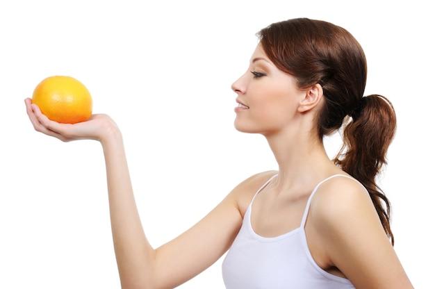 Perfil de uma jovem mulher bonita com laranja isolada