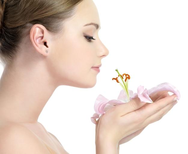 Perfil de uma linda jovem cheirando a flor