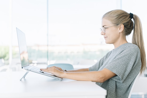 Perfil de uma menina loura com óculos de trabalho com um laptop