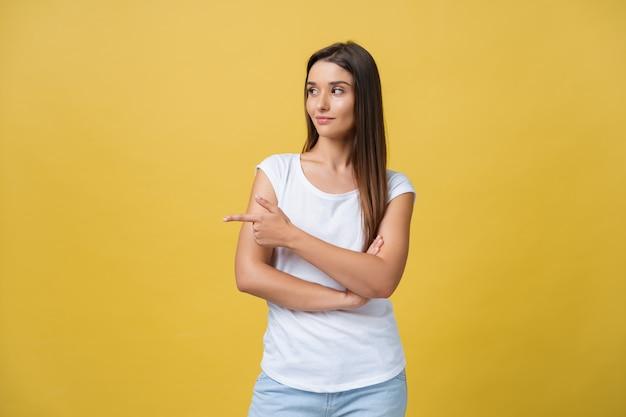 Perfil de uma mulher apontando no espaço da cópia de um anúncio isolado em um fundo amarelo.