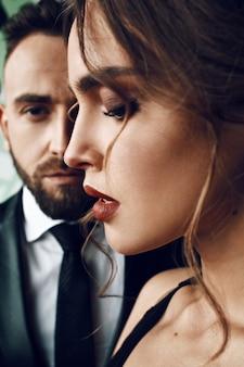 Perfil de uma mulher com lábios vermelhos de pé diante de um homem