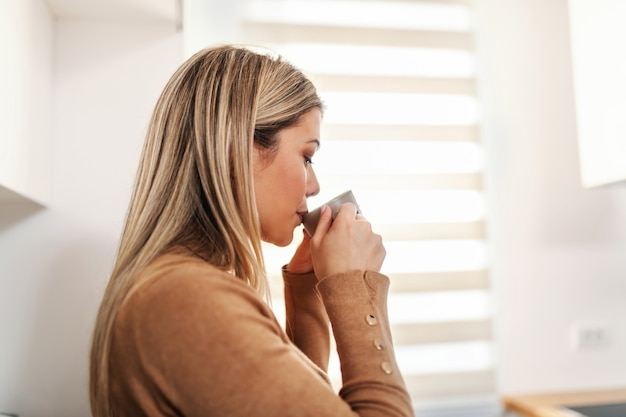 Perfil de uma mulher loira atraente em pé perto da janela e bebendo café fresco da manhã arábica.