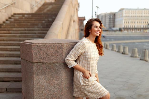 Perfil de uma mulher sorridente com cabelo ruivo, use um vestido bege elegante, posando do lado de fora, com as mãos no bolso.