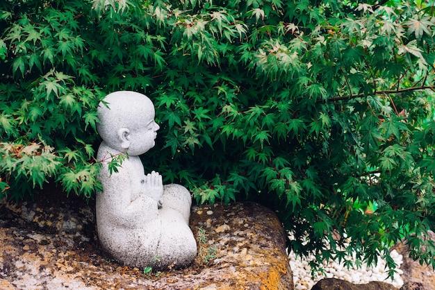 Perfil de uma pequena estátua de buda praying sob a árvore na natureza