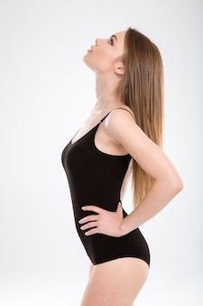 Perfil do close up de uma jovem modelo magrinha em maiô preto posando com as mãos na cintura e olhando para cima