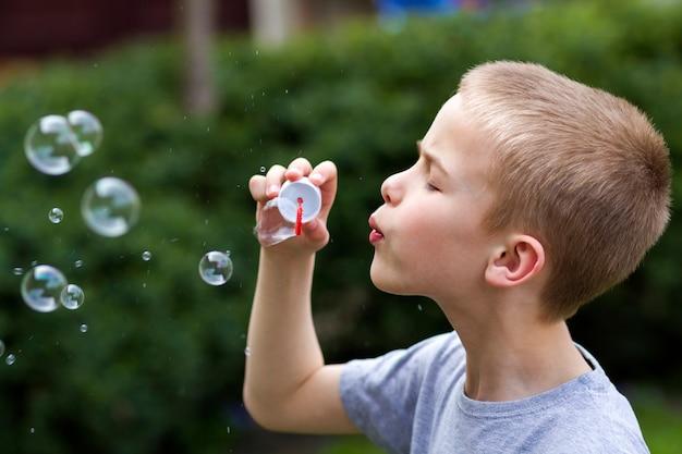 Perfil do menino loiro pequeno bonito bonito da criança com a expressão séria engraçada que funde bolhas de sabão transparentes coloridas fora no fundo verde borrado do verão. alegria do conceito de infância descuidada.