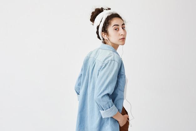 Perfil do modelo feminino bonito, segurando a mão no bolso, ouvindo música ou áudio livro enquanto posava dentro de casa, com expressão de rosto confiante, olhando com apelo. música e relaxamento