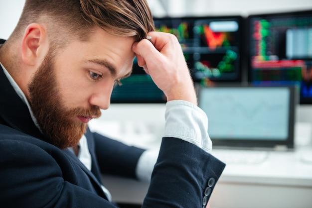 Perfil do pensativo jovem empresário barbudo sentado e pensando no escritório