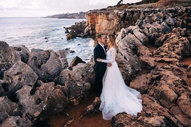 Perfil dos recém-casados nos braços um do outro com os olhos fechados