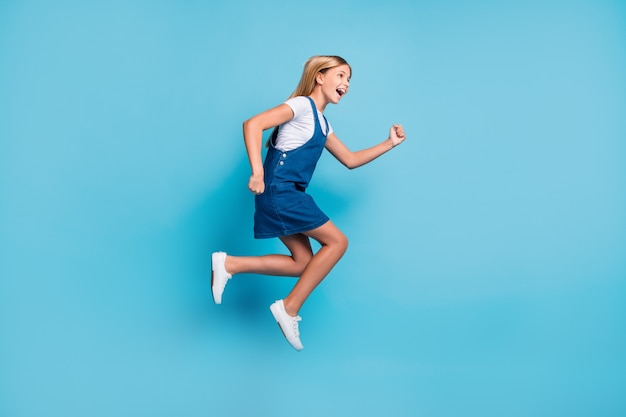 Perfil foto em tamanho grande de uma menina loira engraçada alegre pulando tênis com vestido de t-shirt de desgaste do grito isoladas no fundo da cor azul pastel