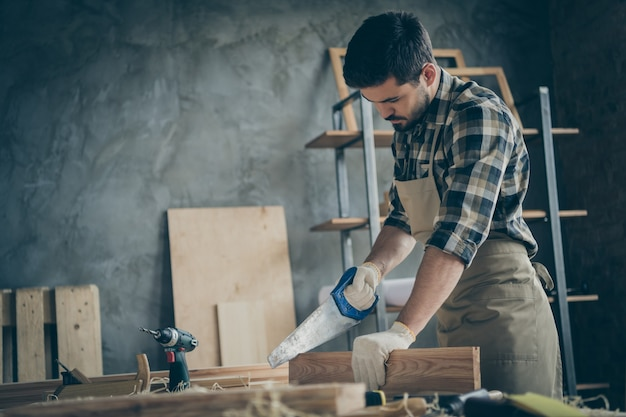 Perfil lateral sério, confiante, homem focado, cortando pedaços desnecessários de um bloco de madeira com serra