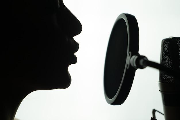 Perfil preto e branco de uma jovem mulher cantando no microfone redondo.