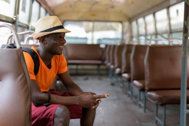 Perfile a vista do homem jovem turista feliz sorrindo enquanto pensa e segurando o telefone celular enquanto andava de ônibus em bangkok tailândia