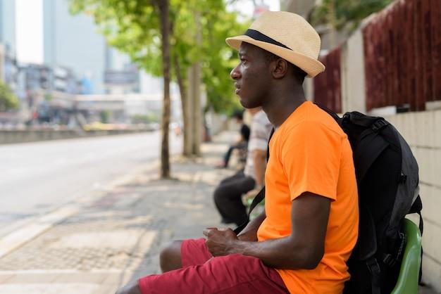 Perfile a vista do homem jovem turista pensando e sentado no ponto de ônibus de bangkok tailândia