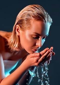 Perfile o retrato da jovem mulher loira que lava seu rosto com agua potável na parede do preto escuro.