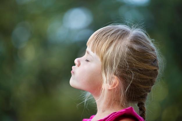 Perfile o retrato da menina loura adorável bonito da criança no vestido cor-de-rosa sem mangas ao ar livre com cabeça levantada e olhos fechados no bokeh borrado da luz ensolarada das árvores verdes.