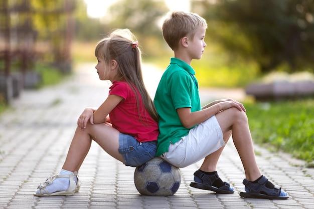 Perfile o retrato de duas crianças louras bonitos, menino de sorriso e menina de cabelos compridos que senta-se na bola de futebol.