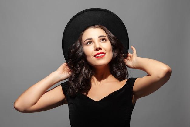 Perfile o retrato de uma senhora sorridente bonita que veste um chapéu preto e olha para cima