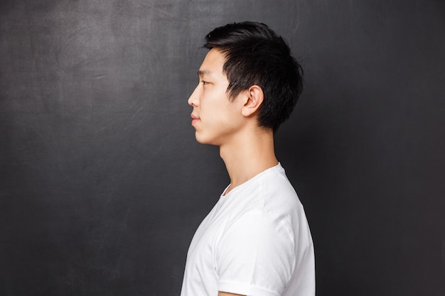 Perfile o retrato do modelo masculino asiático novo no t-shirt branco que sorri ocasionalmente em pé e olhando sobrando do estúdio, esperando na fila, conceito de pessoas e estilo de vida