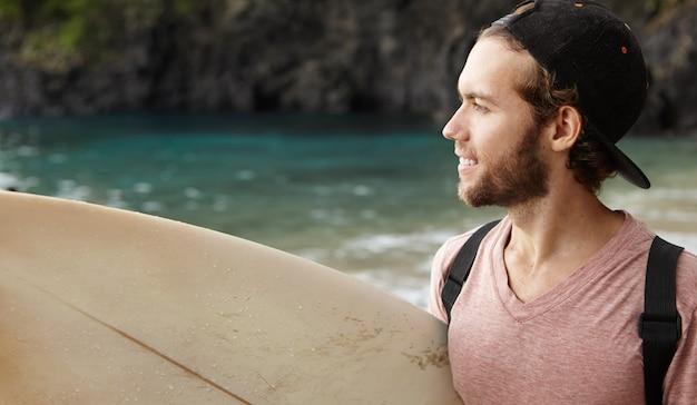 Perfile o retrato do surfista de bom humor, carregando sua prancha de surf debaixo do braço, olhando para o mar e sorrindo, tendo um olhar pensativo