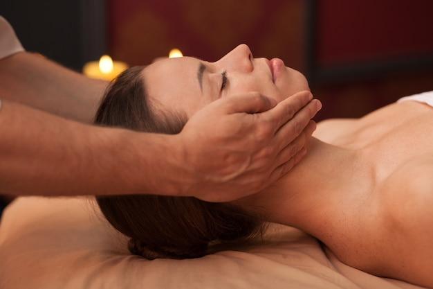 Perfile próximo acima de uma mulher bonita que aprecia a massagem de cara no centro de spa. esteticista, massageando o rosto de uma jovem fêmea. mulher deslumbrante relaxante no centro de beleza, recebendo massagem de aperto da pele