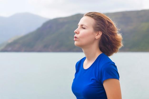 Perfile, retrato da vista lateral da mulher relaxada que respira o ar profundamente fresco no mar, oceano nas montanhas. calma garota ruiva jovem ruiva relaxante, meditando ao ar livre, fazendo exercícios de respiração. copie o espaço
