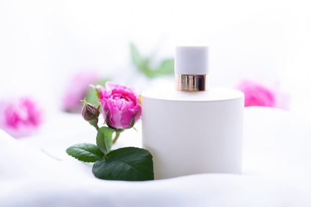 Perfume branco com flores sobre fundo claro