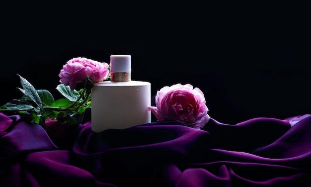 Perfume com flores sobre fundo escuro