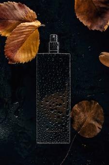Perfume com folhas secas em fundo preto