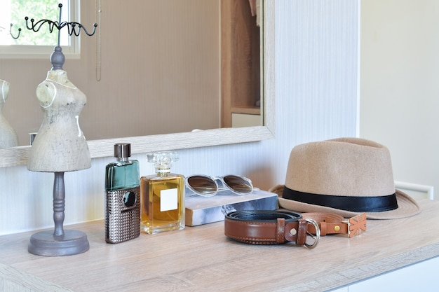 Perfume de chapéu castanho e cinto de couro