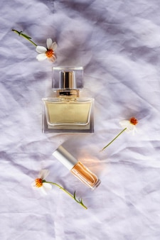 Perfume dourado e frascos de perfume em fundo branco