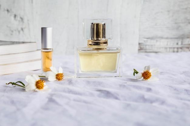 Perfume dourado e frascos de perfume na mesa branca