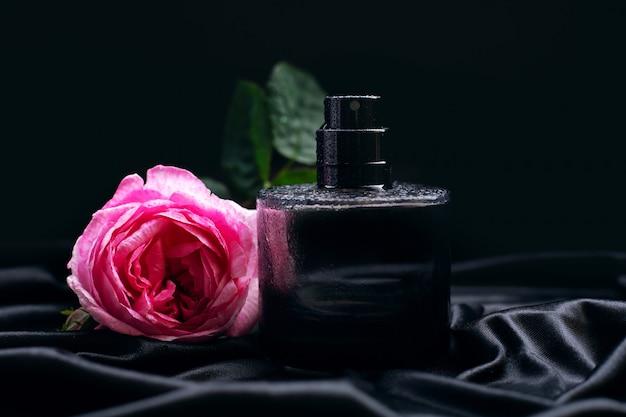 Perfume e flor rosa em fundo preto