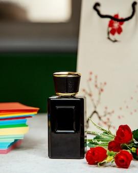 Perfume em garrafa preta em cima da mesa
