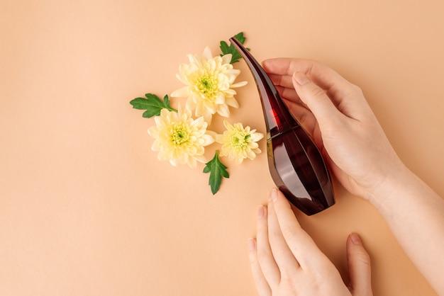 Perfume em mãos femininas, flores e folhas verdes em bege