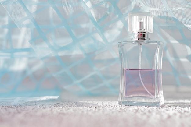 Perfume em um fundo de tecido azul cheiro