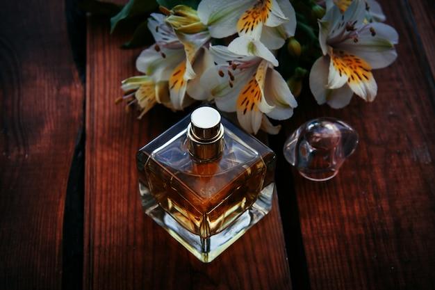 Perfume feminino com flores sobre fundo de madeira
