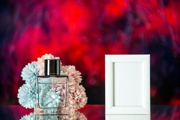 Perfume feminino de frente para uma pequena foto branca com flores no local de cópia de fundo desfocado azul escuro