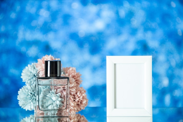 Perfume feminino de frente para uma pequena moldura branca com flores no espaço livre azul de fundo desfocado