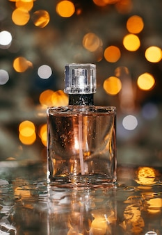 Perfume feminino em fundo dourado bokeh com gotas de água e reflexo