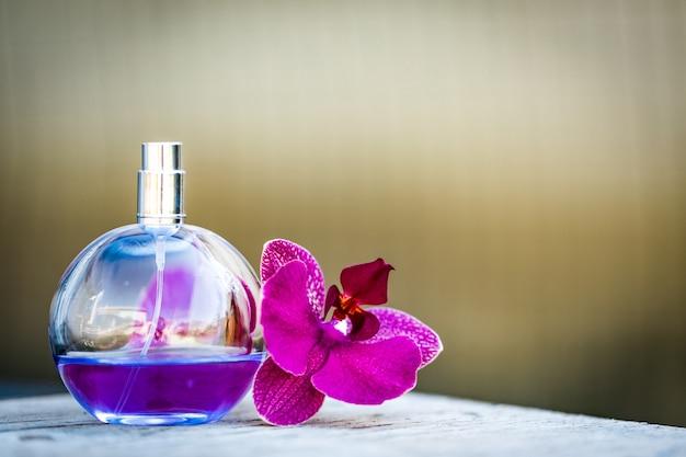 Perfume feminino em linda garrafa com orquídeas em bokeh de fundo.