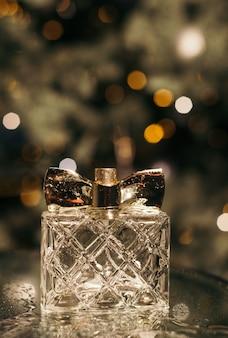 Perfume feminino em uma mesa de vidro com gotas de água no fundo de uma árvore de natal com luzes e bokeh