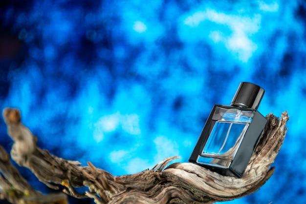 Perfume masculino de vista frontal em galho de árvore seca isolado em fundo azul claro com espaço livre