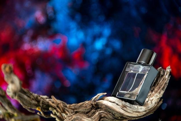 Perfume masculino de vista frontal em galho de árvore seco isolado em espaço livre de fundo abstrato vermelho azul