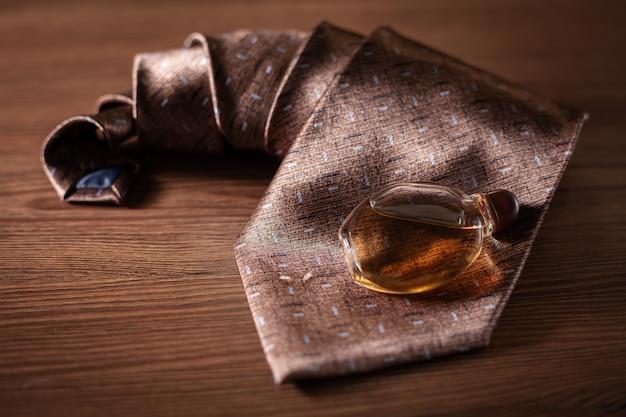 Perfume masculino e gravata numa superfície de madeira