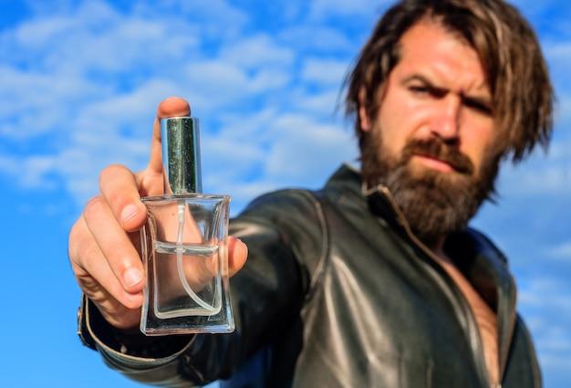 Perfume masculino. homem barbudo bonito com frasco de perfume. foco seletivo.