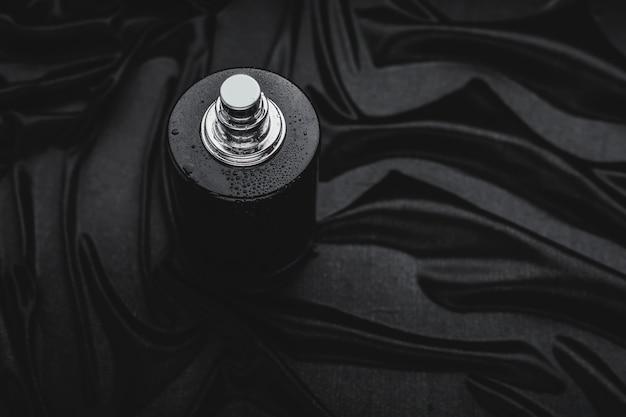 Perfume preto em um fundo de tecido preto