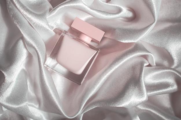Perfume rosa sobre fundo de tecido de seda