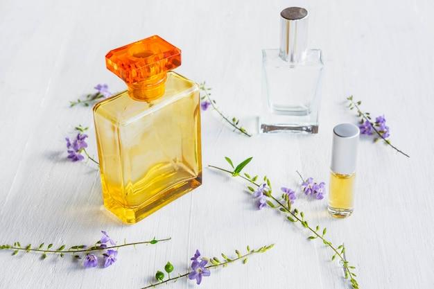 Perfumes e frascos de perfume em um branco de madeira