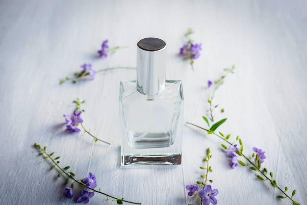 Perfumes e frascos de perfume em um fundo branco de madeira